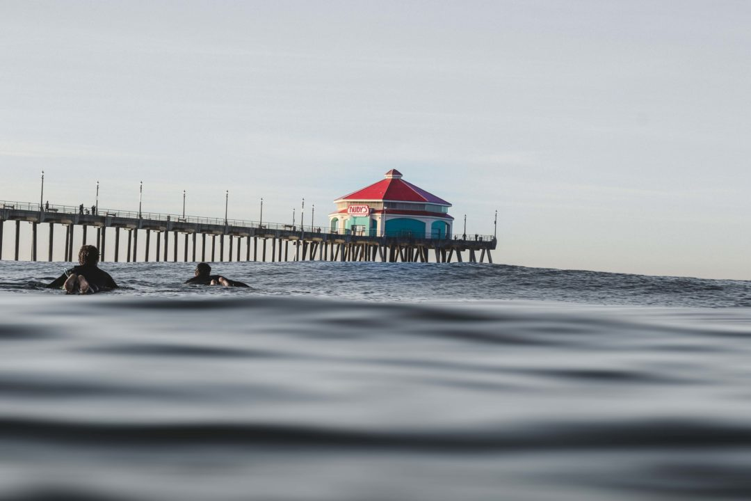 surfers in wetsuits paddling out on a glassy day to the surf break on the north side of the huntington pier. Rudy's red roofed diner sits on the horizon of the pier.