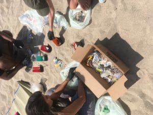 four volunteers at a Daana Blue beach cleanup on Venice Beach sorting though found beach trash to find micro plastics and recyclables