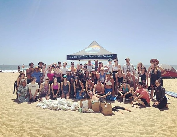 "About 40 beach cleanup participants on Venice Beach posing behind a large pile of collected beach trash, in front of a black tent that says ""wavehuggers: an ocean-conscious surf school"""