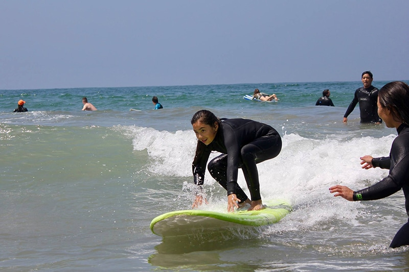 pre-teen girl in black wetsuit crouching on lime green foam top surfboard at a one wateshed youth event in southern california