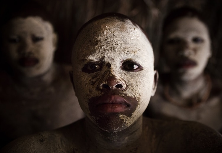 three South African at the camera wearing a white mud mask flaking off their face