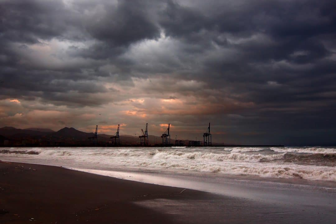 photo of 5 oil rigs lining a stormy coastline at sunset
