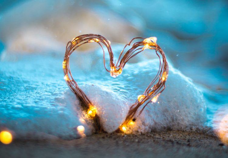 a heart made out of copper string lights standing on the beach as it fills with sea foam from a southern california wave