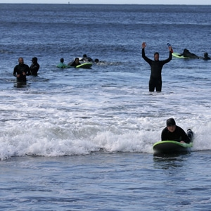 a dozen surf instructors and kids at a california surfbreak participating in a surf charity event that uses recycled wetsuits