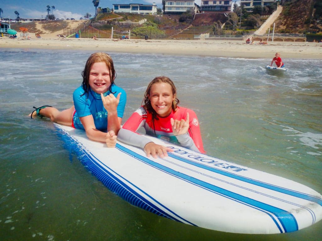 young girl smiling while lying on board throwing a shaka with her professional surf instructor by her side