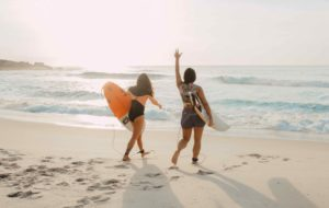 Two female surfers walking on a southern california beach into the pacific ocean with short boards under their arms, one of them waves to friends in the lineup
