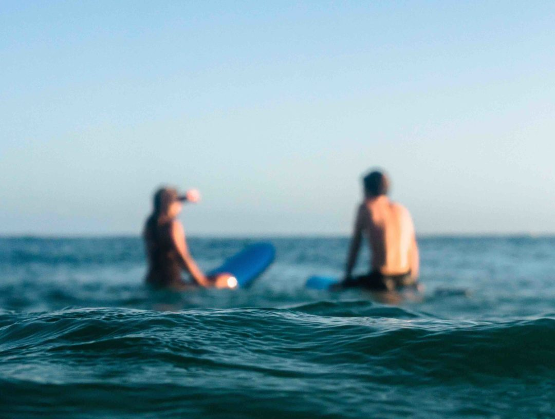 blurry shot of the back of a male and female surfer in swimsuits sitting on soft top surfboards at a socal surf break waiting for a wave