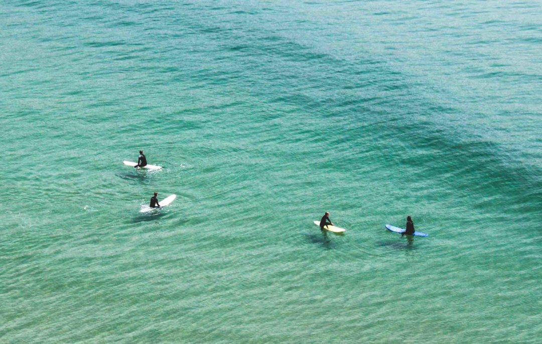 ariel shot of 4 surfers in wetsuits sitting on longboards waiting for waves in a smooth, shallow, green beginner surf break in southern california