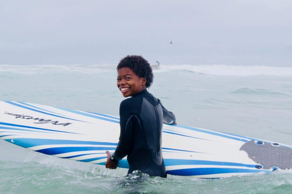 young elementary school, pre-teen age boy smiling while holding a soft surf board in the water