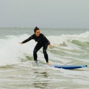 Young, brunette woman smiling while riding surfboard on a seafoam wave in in California near Manhattan Beach