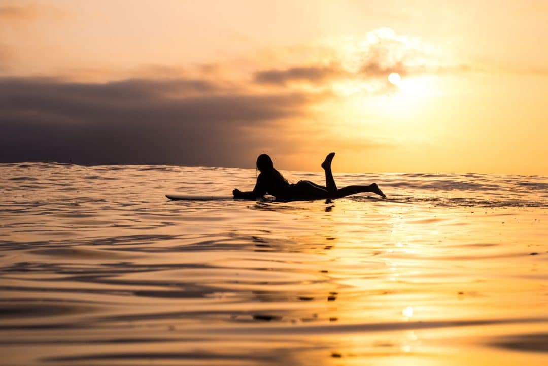 silhouette of woman woman lying down on her floating surfboard at a surfbreak near newport beach at sunset