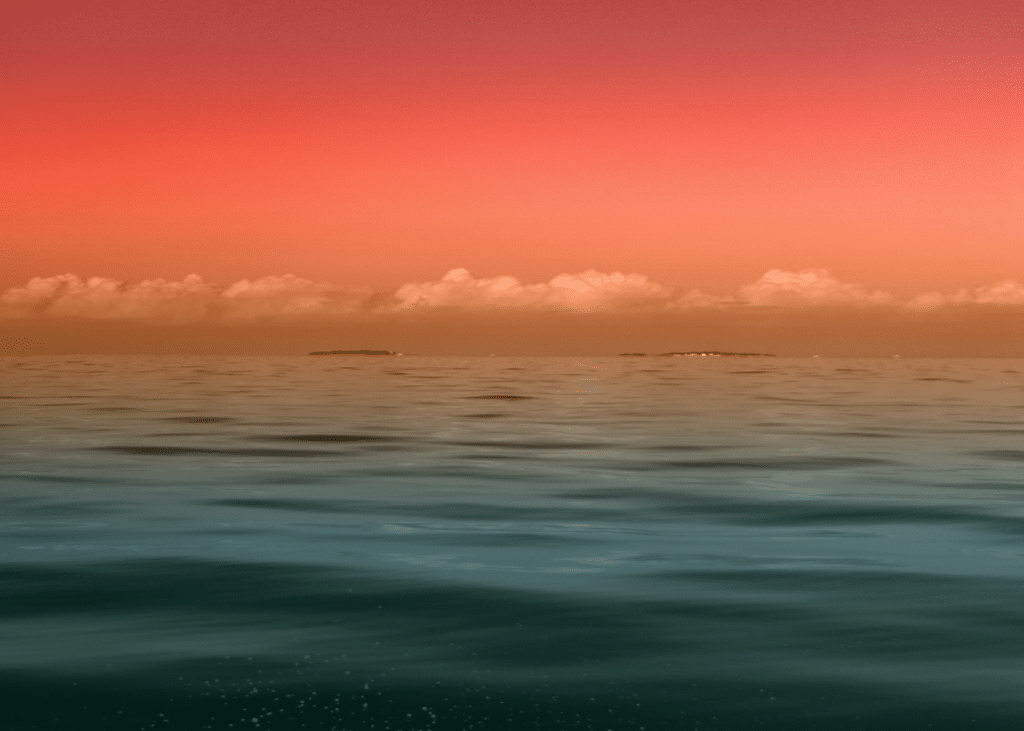Calm, Teal green waves, and an orange and bright red sunset looking over the water at small islands in the difference