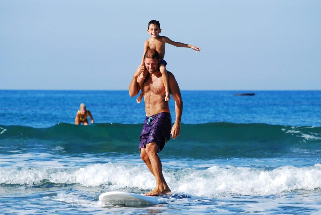 young boy riding on the shoulders of a man who's surfing on a small wave near santa monica california
