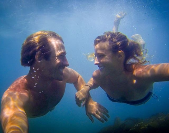 a young california surf couple holding their breath while diving underwater. They're holding hands and smiling at eachother during a Valentine's surf date in the south bay of los angeles
