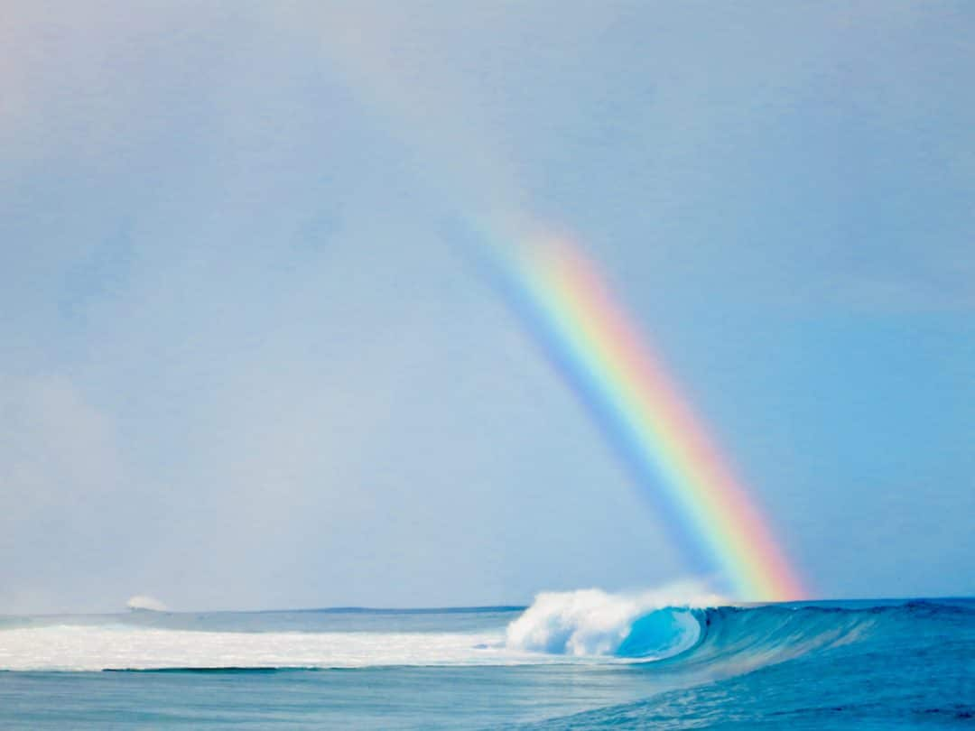 a rainbow arching out the pacific ocean, with a clear blue wave barreling near southern california
