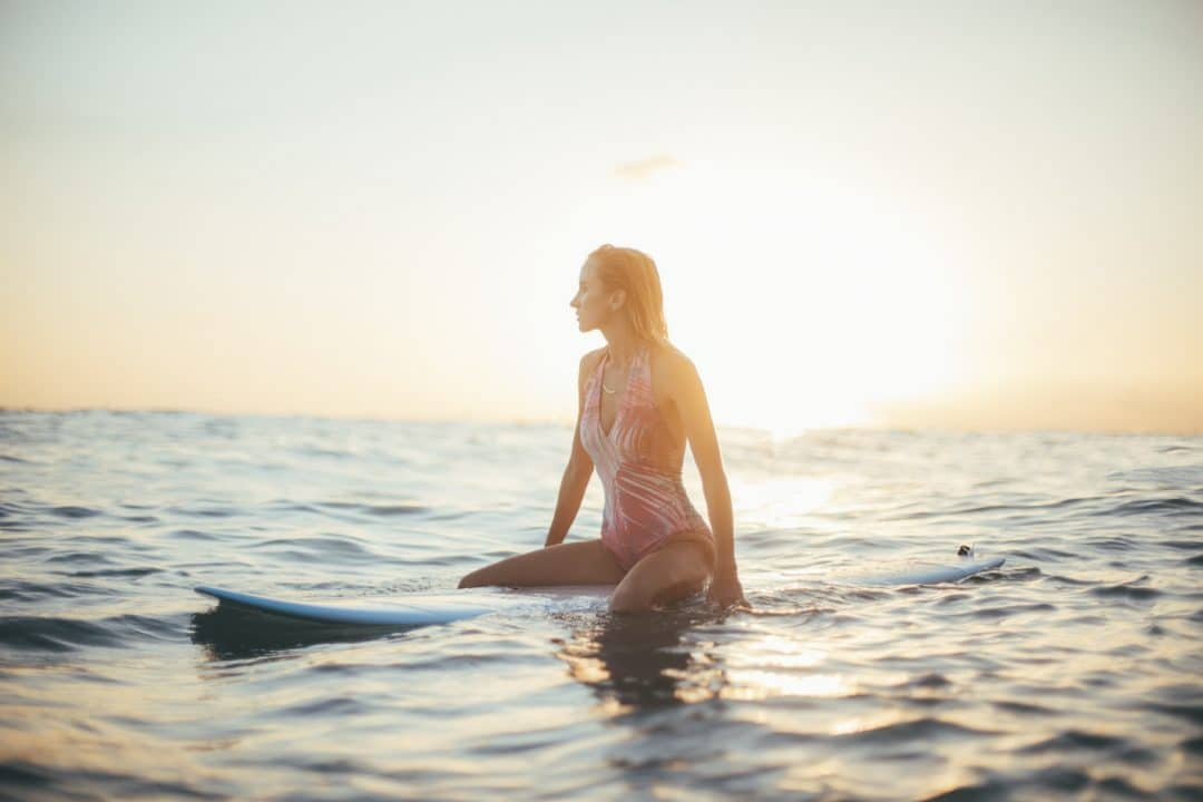 blond woman in a pink one piece swimsuit sitting on surfboard waiting for a wave while looking out at the setting sun