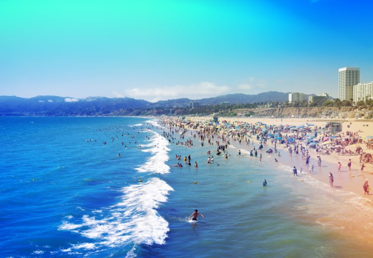 a late summer crowd enjoys the beach and turquoise and blue water with the santa monica mountains in the background