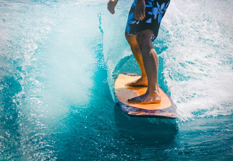 a man in blue flowered boardshorts rides a wooden surfboard on an aqua colored wave in southern california