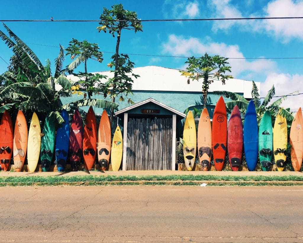 a rainbow of old surfboards lined up like a fence around a house in california