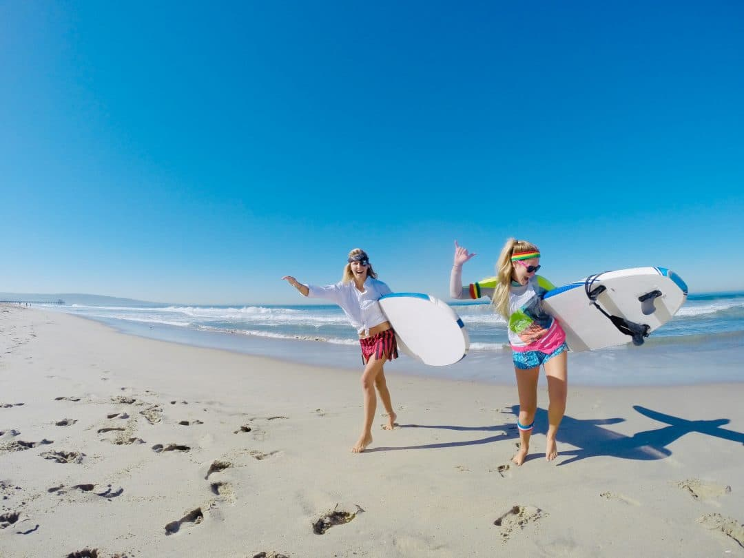 two female surfers dance on the beach with surf boards in south bay los angeles. One wears a pirate costume the other is dressed as an 80s girl.