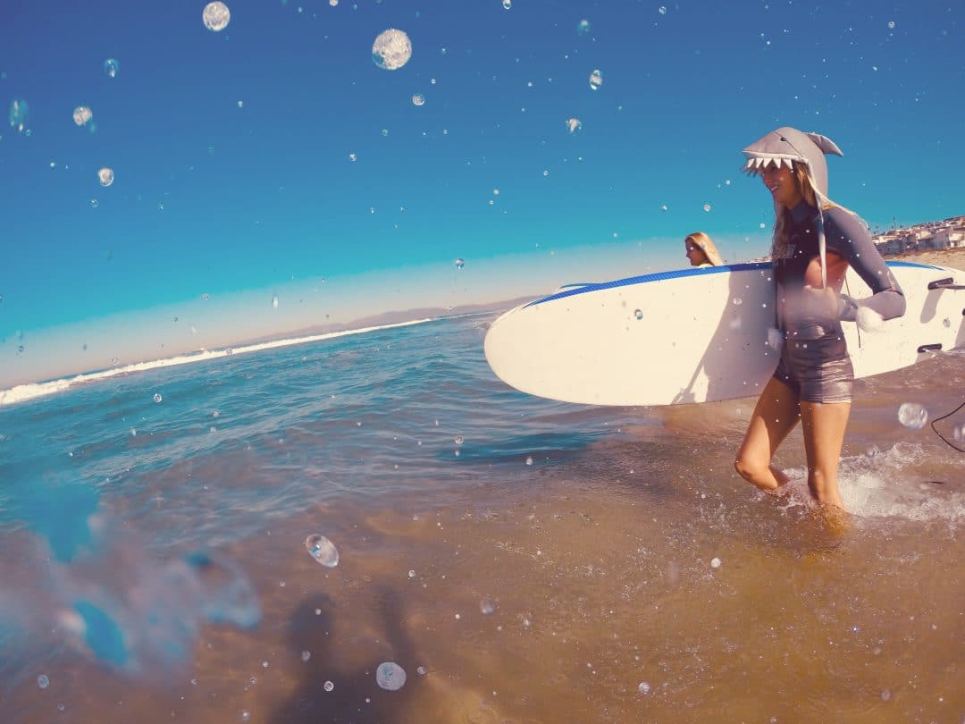 female surfer with a hat that looks like a shark head walks out with a foam surfboard into a blue ocean with mellow waves