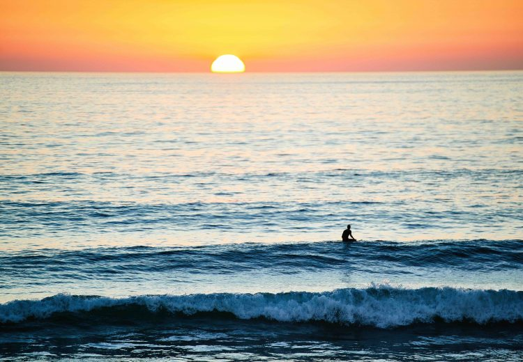 a lone surfer sits beyond the surfline looking at a pink and yellow sun setting on the horizon in southern california