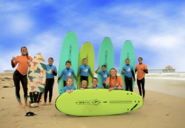 A group of 8 kids stand with aqua and lime surfboards smiling for the camera at huntington beach with their 3 surf instructors