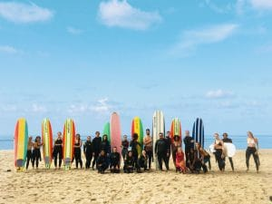 large group of community surf class beginner surfers in Santa Monica posing with colorful soft top surfboards