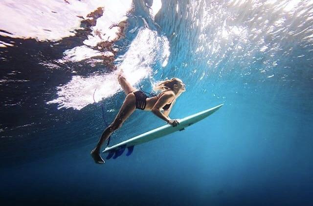 Wavehuggers founder Helina duck dives under a large barreling wave on her short board.