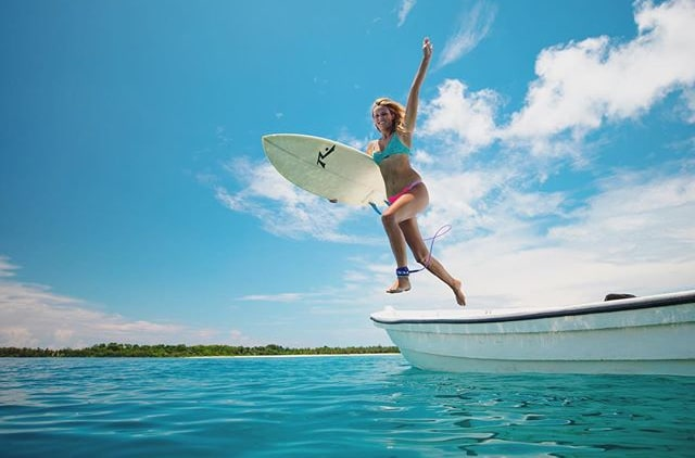 wavehuggers surf school founder Helina beck jumps off a boat into aqua water with her short board