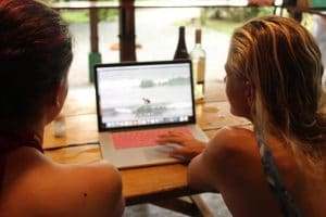 pro surfer holly beck sits at a table reviewing a student's waves as a part of a video surf coaching session