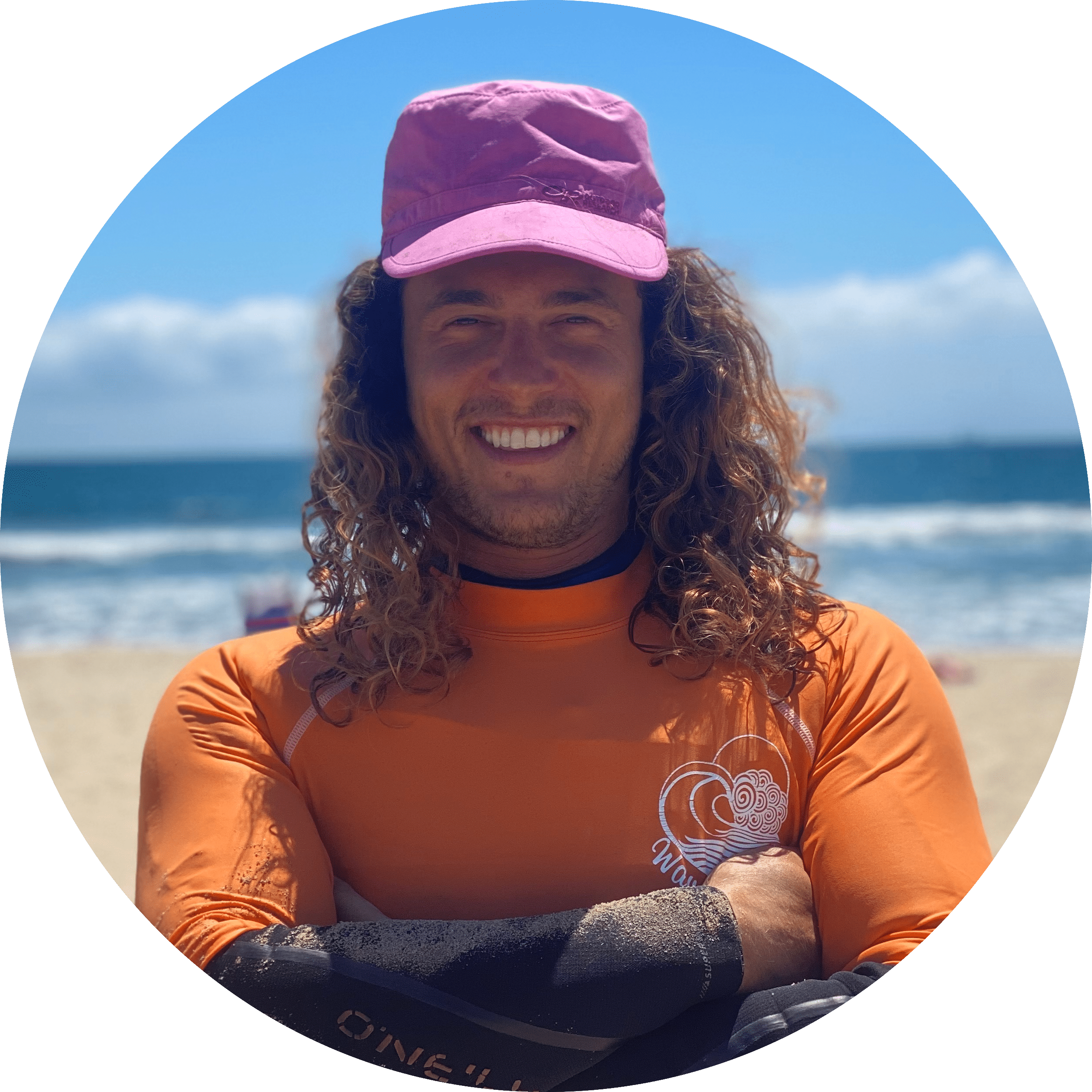 James, a wavehuggers surf instructor smiles in front of the surf break at Huntington Beach in Orange County