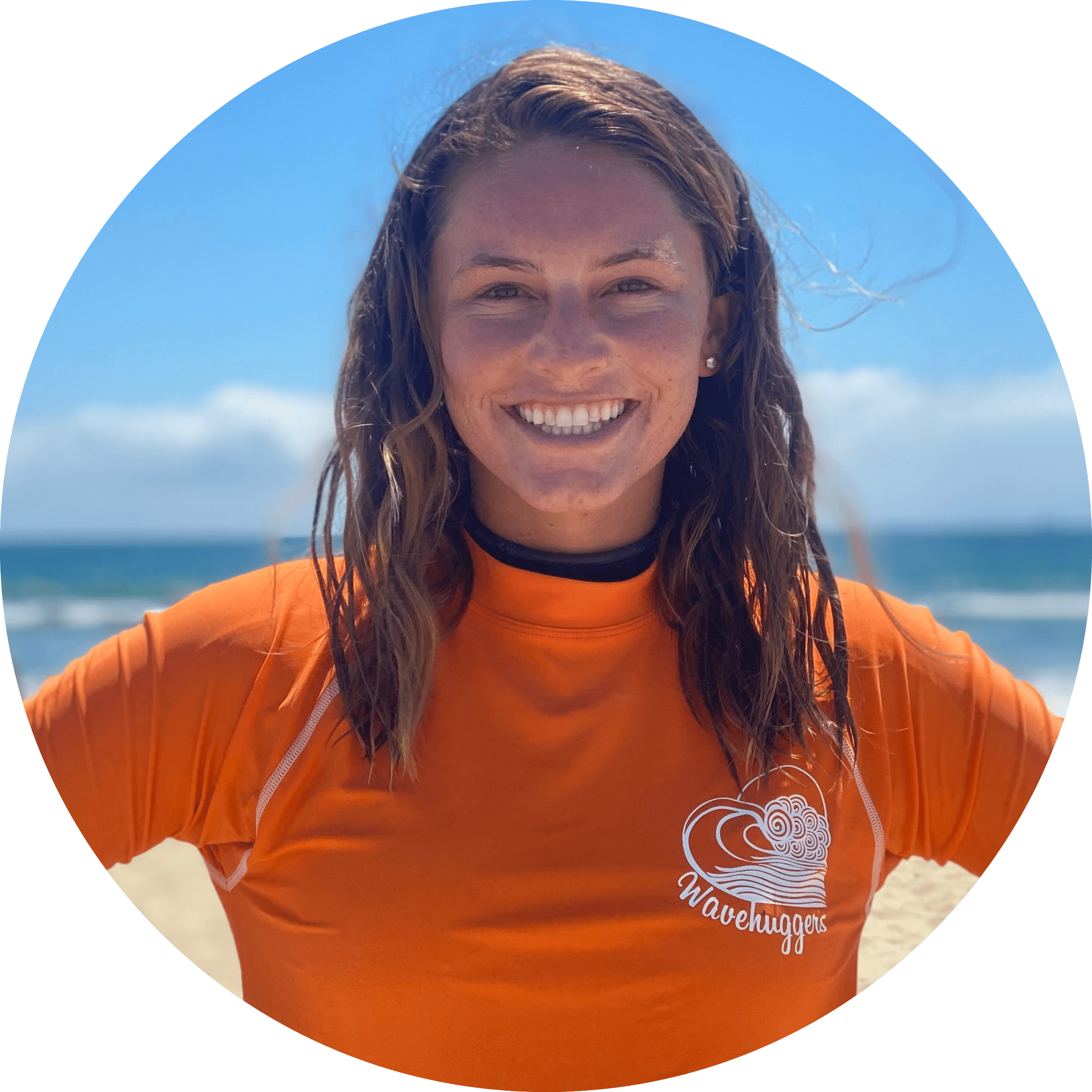 Damie, a young female surf camp counselor at wavehuggers huntington beach camp smiles in front of the the ocean