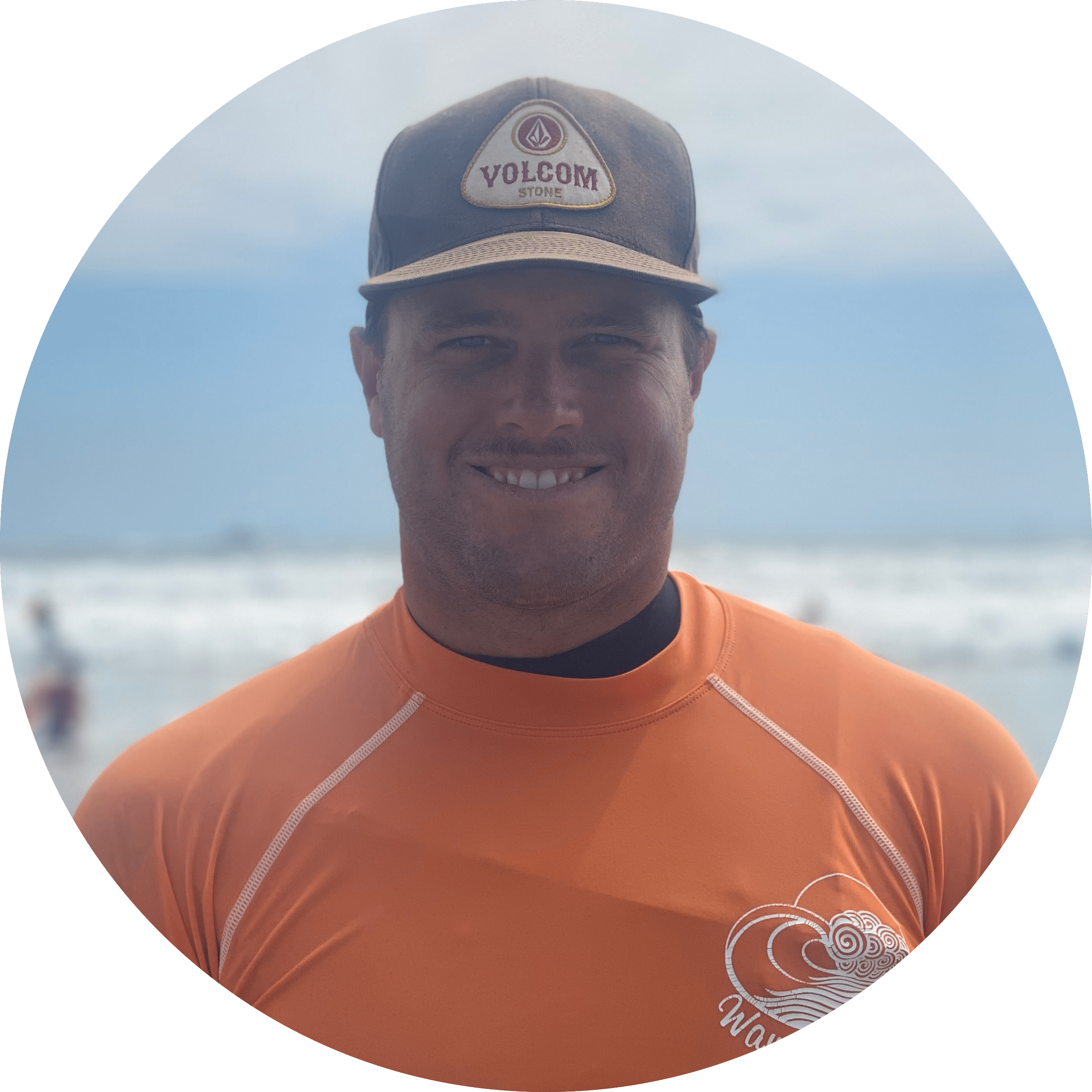 Max, a wavehuggers surf instructor smiles in front of the surf break at Newport Beach in Orange County
