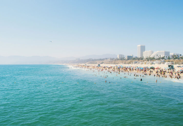 beach goers play in the turquoise water on a warm day in santa monica