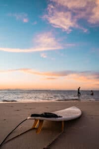 white short surfboard left on beach in front of ocean at sunset while people play in the waves in the distance
