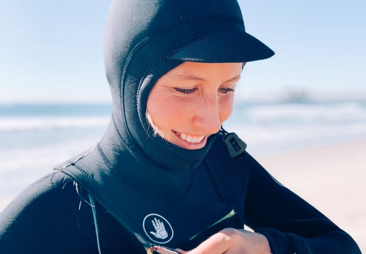 wavehuggers owner helina zips the hood to her 4/3 wetsuit before surfing winter waves in huntington beach