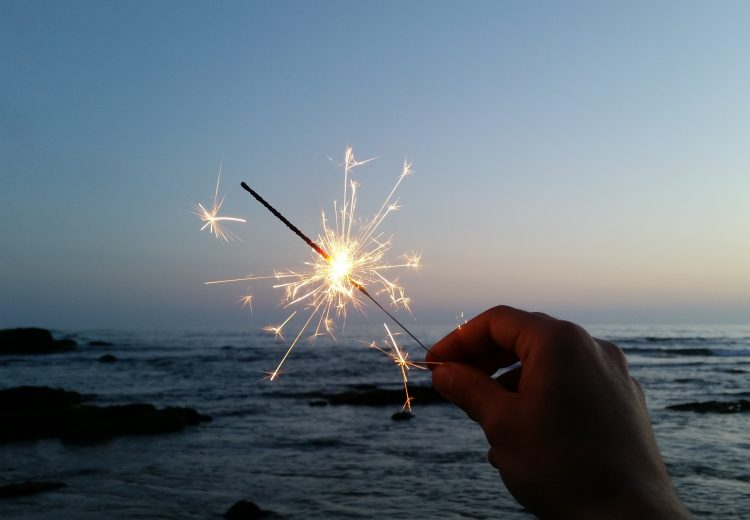 a hand holds up a fireworks sparkler in front of an evening ocean
