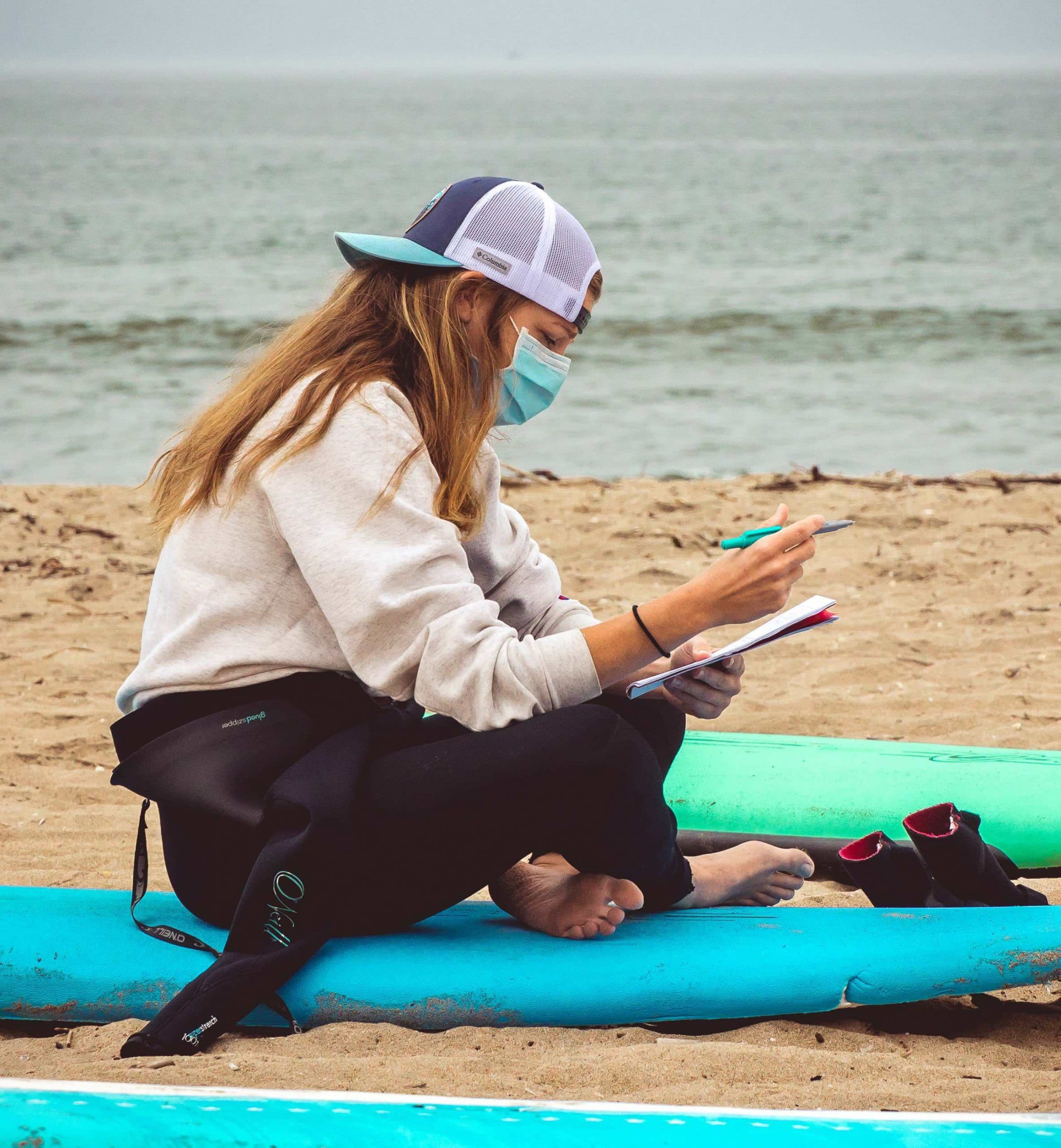 photo of a surf therapy participant sitting on a surfboard on the beach, writing in a journal