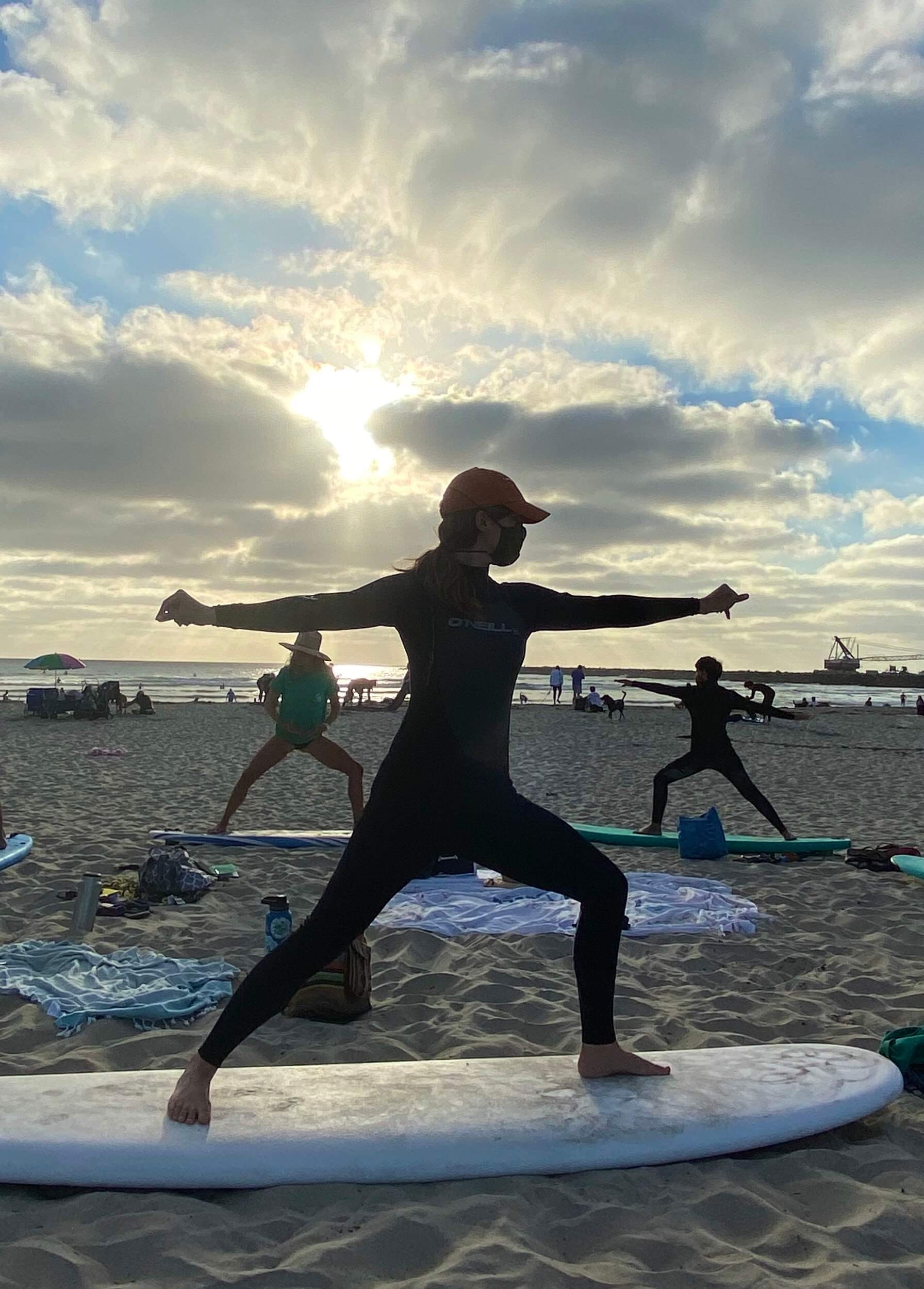 surf therapy participant practices her surf stance on her board on the beach at sunset